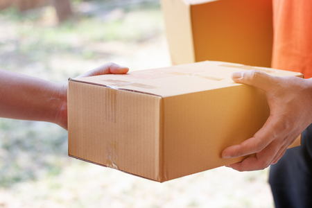 Customer signing document and receiving the parcel from delivery man. Stock Photo