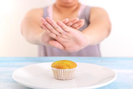 dikke vrouw die cupcake of ongezond voedsel afwijst. Gezondheidszorgconcept.