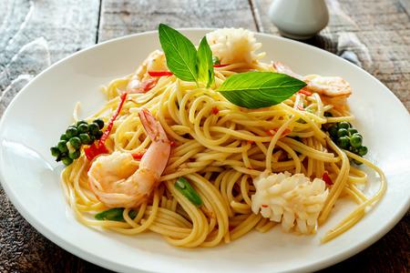 spaghetti piccanti con frutti di mare sul piatto.