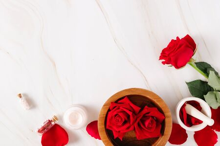 Spa product with rose cream and Rose petals on a marble background.