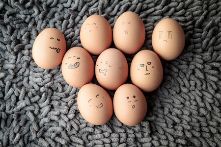 funny eggs with face feeling on the carpet. Stock Photo