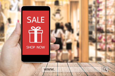 Hand holding smart phone with sale paynow on screen and www. search bar over blur people in the shopping mall background, business and financial concept. Stock Photo