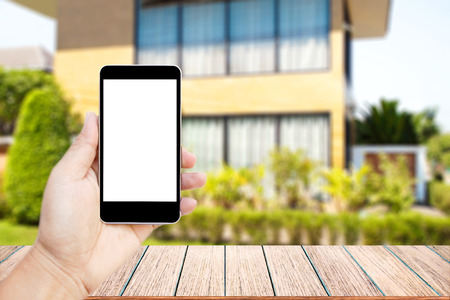 Mock up image of hand holding black mobile phone with blank white screen, Empty wood table top on blurred images home garden for background, perspective wood can be used for display products.