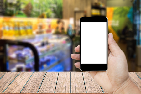 Mock up image of hand holding black mobile phone with blank white screen, Empty wood table top on blurred images coffee shop for background, perspective wood can be used for display products. Stock Photo
