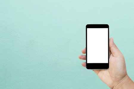 Mock up image of hand holding black mobile phone with blank white screen, Isolated on vintage wall background with copy space for adding more text. (Clipping path included for design work)