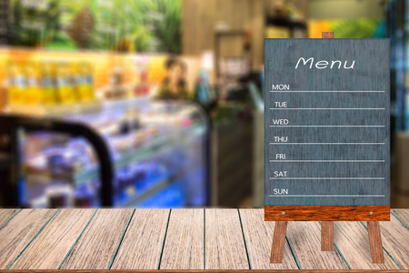 Wooden menu display sign, Frame restaurant message board on wooden table, Blurred image background, Template mock up for adding your design and leave space beside frame for adding more text.