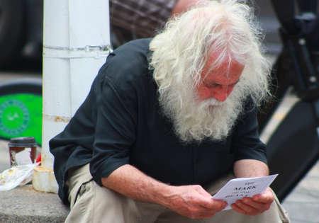 Toronto, Canada- July 07, 2018 Homeless man sitting on a street reading