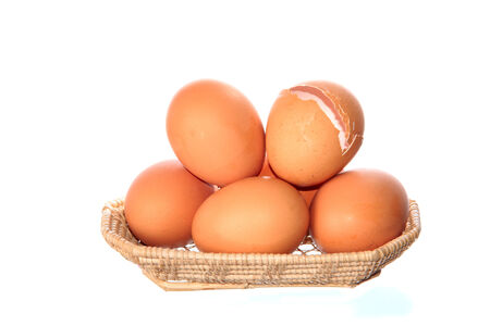 many fresh chicken eggs in wicker basket isolated on white background photo