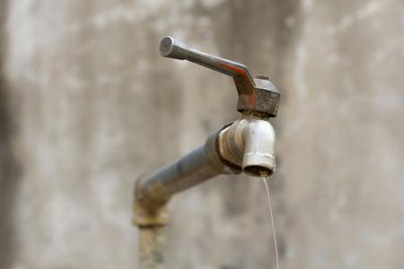 水を無駄にされてを示す水のしたたる蛇口