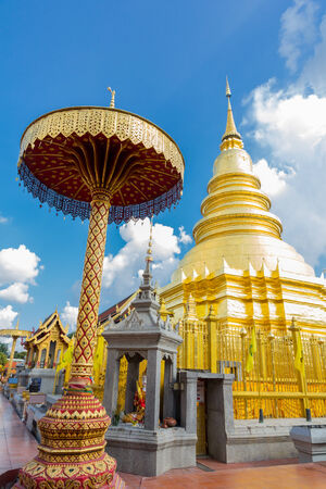 The golden pagoda with blue sky at Hariphunchai temple, Lampang Province, Thailand .