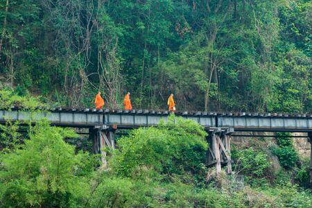 limosna: monjes budistas jovenes que caminan limosnas de la mañana en las vías del ferrocarril en la provincia de Kanchanaburi, Tailandia