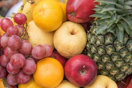 fruits in a basket: Close-up of a large cluster of fruits basket, Grapes, oranges, bananas, apples, pineapple, wheat.