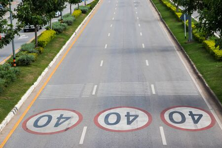 slower: Speed limit printed on the asphalt in thailand Stock Photo