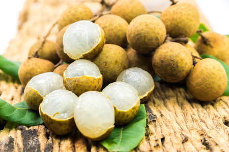 Fresh ripe longan fruits and leaves on a wooden board