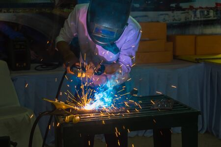 protective mask: welder with protective mask welding metal and sparks