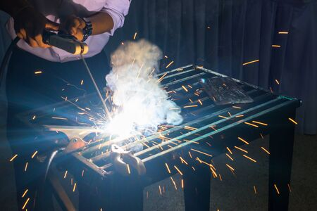 erecting: welder with protective mask welding metal and sparks