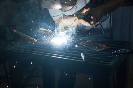 erection: welder with protective mask welding metal and sparks