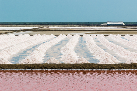 evaporating: Farm salt or salt on a blue background with red water before evaporating salt.