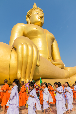 priests: Priests and seminarians and people pray to big golden buddha on blue sky in Angtong, Thailand Editorial