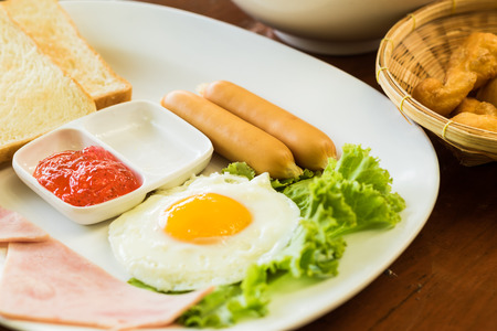 breakfast with fried eggs, mush, patongko, sausages, toasts and fresh salad