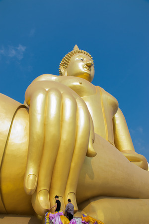 people pray to big golden buddha on blue sky in Angtong, Thailand