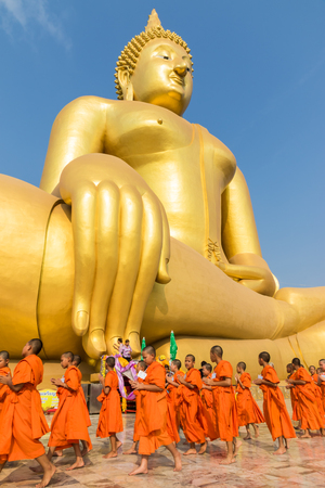Priests and seminarians and people pray to big golden buddha on blue sky in Angtong, Thailand Editorial