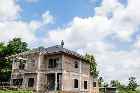 Building & Construction and roof in progress to new house on blue sky background in Thailand