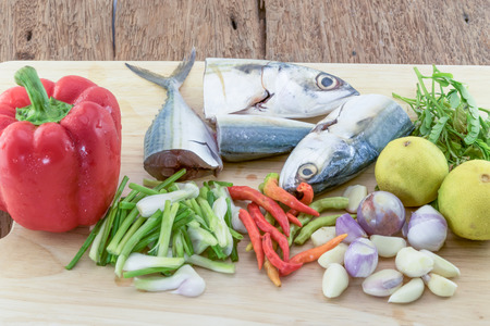 side view of Fresh Raw Whole Fish Mackerel on Slate Cutting Board Surrounded by Fresh Herbs and Spices for Seasoning and Garnishing