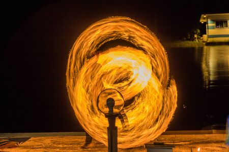 Fire dancing show fireball show amazing at night. Swinging fire in full moon thailand. 스톡 콘텐츠