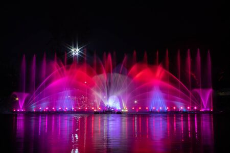Beautiful fountain show with reflection on water at night.