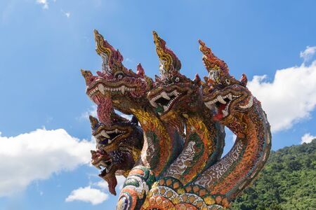 Many Naga Heads on blue sky background. Naga heads along the Naga steps in Buddhist temples are dramatically ornamented and extensively used in Thai temples or Wat Thai. 写真素材