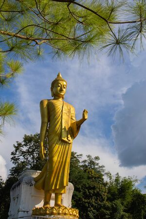 The standing golden buddha statue with  blue sky background. Loei, Thailand