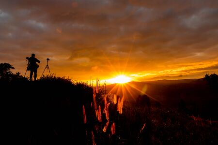 silhouette of photographer on beautiful  sunrise and beautiful sky in the mountain at Loei Provice,Thailand.