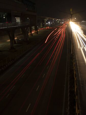 Speed Traffic light trails on highway, long exposure, urban background and dark sky