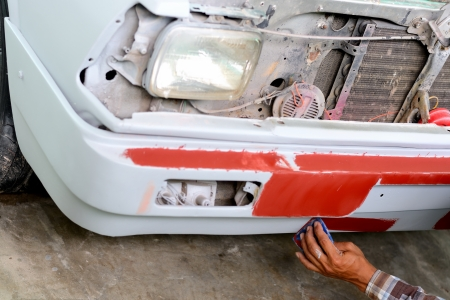 Auto mechanic preparing the front bumper of a car for painting  photo