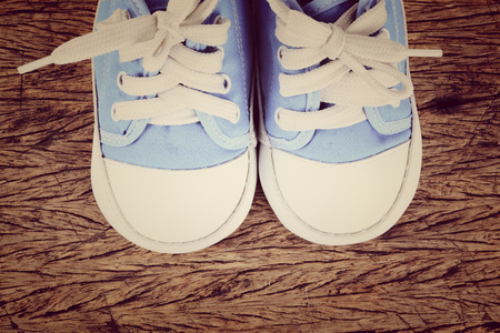 baby clothes: Baby sneakers on wood background