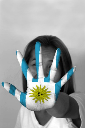 uruguay flag: woman with her hands signaling to stop and Uruguay flag