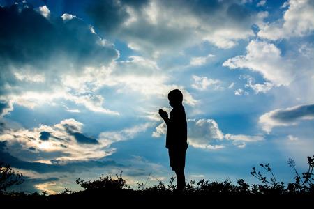 manos levantadas al cielo: Kid orar, concepto sillhouette Foto de archivo