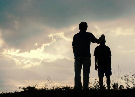 Pai e filho olhando para o futuro, conceito silhueta Imagens