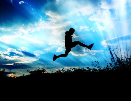Kleine jongen springen naar de lucht en gelukkige tijd, Sillhouette concept