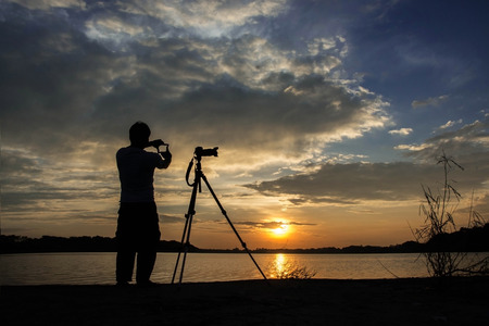 sunspot: Silhouette of photographer with his equipment during sunset hand check composition