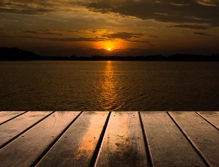 Houten platform naast het meer met zonsondergang