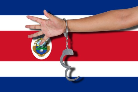 bandera de costa rica: handcuffs with hand on Costa Rica flag Foto de archivo
