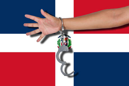 dominican republic: handcuffs with hand on Dominican Republic flag