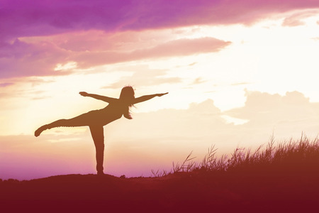 Silhouette Yoga woman in serene sunset at mountain Foto de archivo
