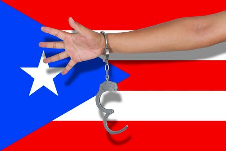 puerto rico: handcuffs with hand on Puerto Rico flag Stock Photo