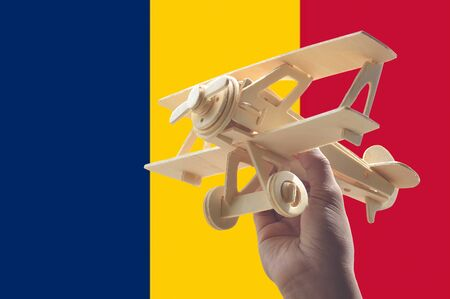 chad flag: Hand holding airplane plane over Chad flag, travel concept