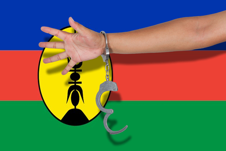 new caledonia: handcuffs with hand on New Caledonia flag Stock Photo