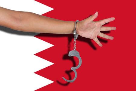 bahrain: handcuffs with hand on Bahrain flag Stock Photo