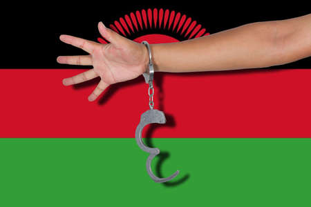 malawi flag: handcuffs with hand on Malawi flag Stock Photo